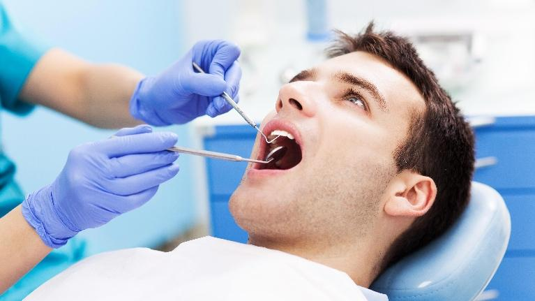 Man having teeth cleaned | The Dental Care Center